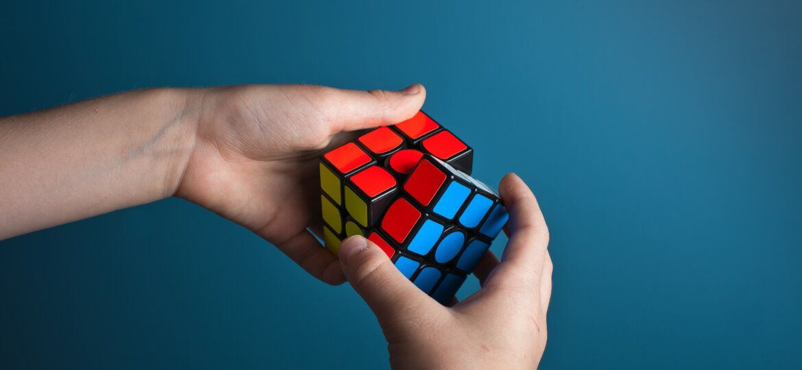 Shot of hands holding an almost solved Rubix cube