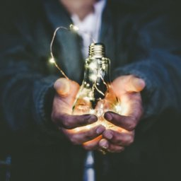 Close up of outstretched hands cupping a glowing lightbulb strung with fairy lights.