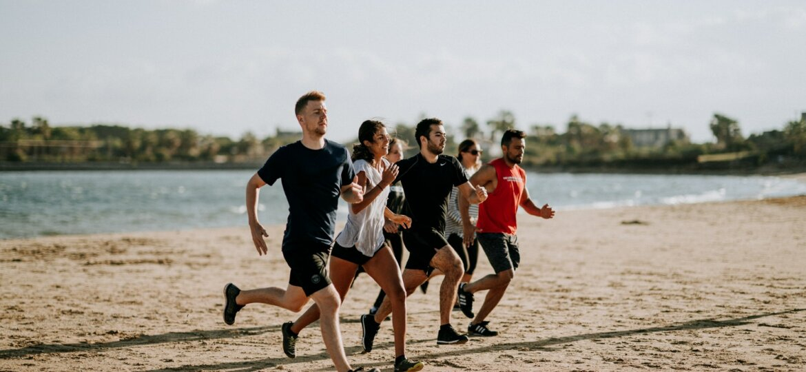 A pack of people running on a beach