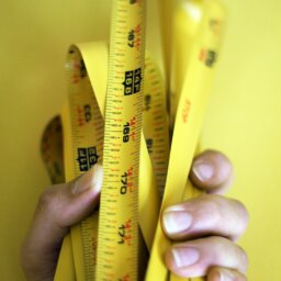 A hand holding a bunched measuring tape against a yellow background