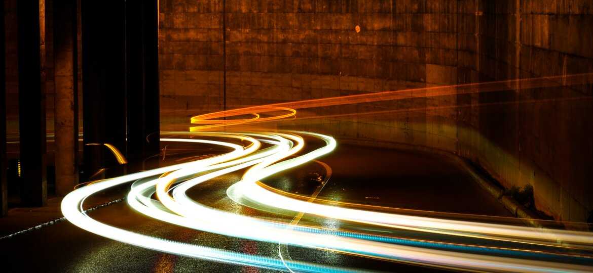 Time lapse photography showing streaks of light passing through a gleaming wet tunnel