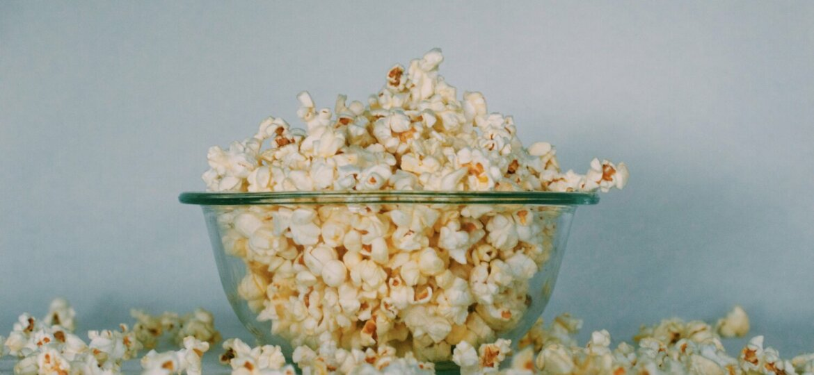 Popcorn overflows a clear bowl