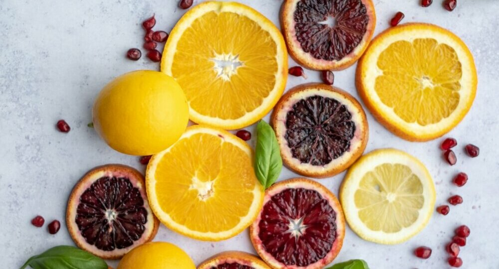 Citrus fruits (whole and cut) arranged on a flat surface in a diagonal pattern