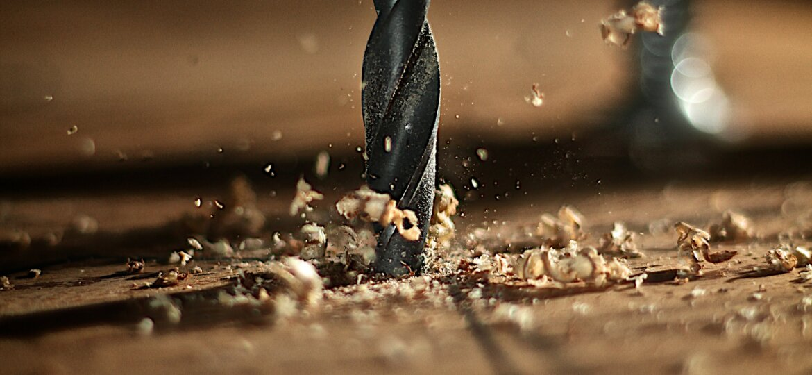 A close up of a drill biting into wood