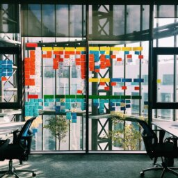 Colourful cards stuck to a glass wall, in a pattern that denotes planning in progress