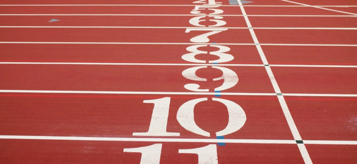 An image of a starting line on a running track, ranging form 1 at the back to 11 in the foreground