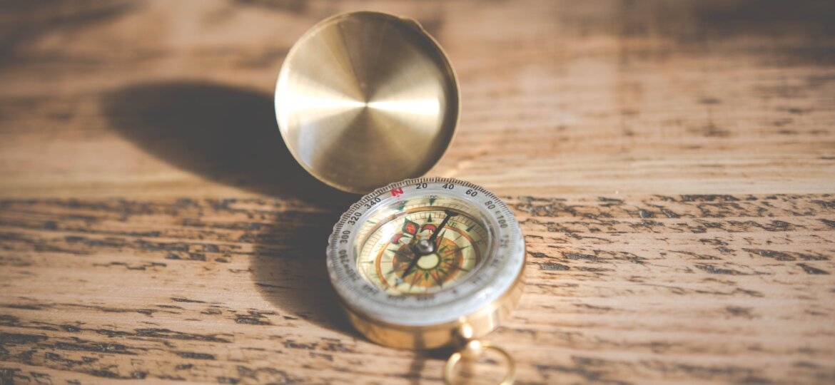 A compass shining on a wooden table