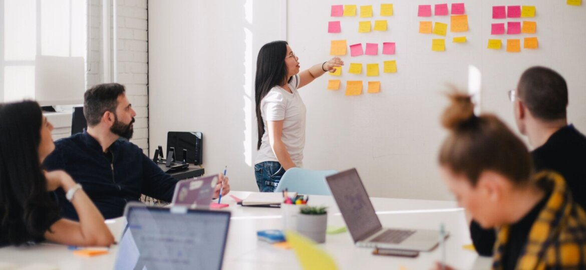 Colleagues gather around a table, with the meeting leader gesturing at post it notes on a wall