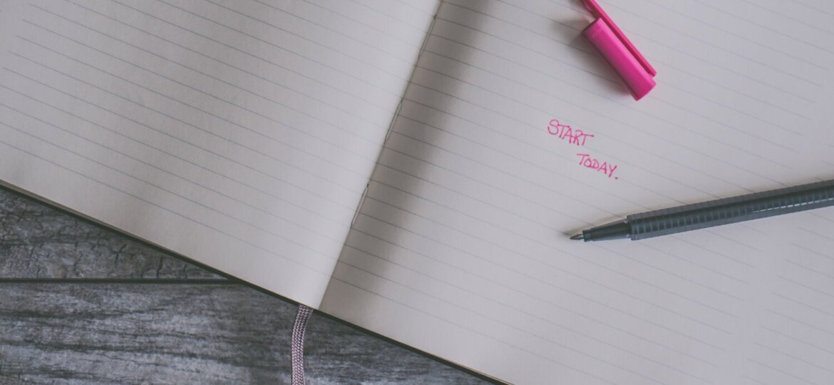 """A notebook with a pen and pencap resting on top. Written on the open page are the words """"start today"""" in pink."""