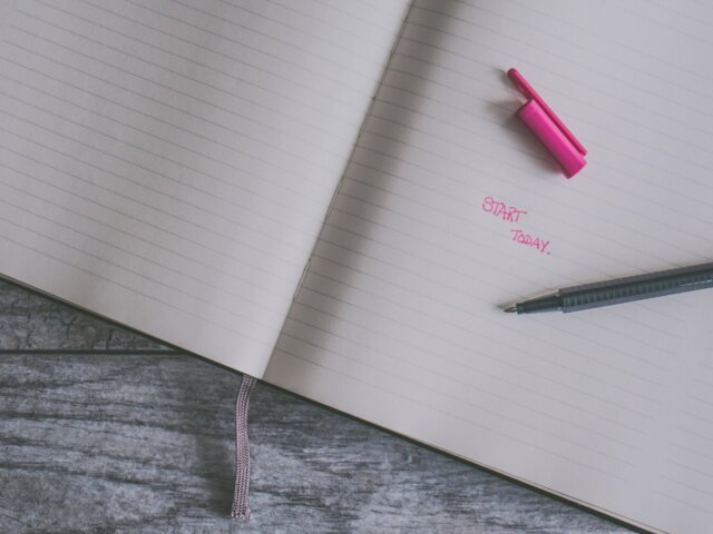"A notebook with a pen and pencap resting on top. Written on the open page are the words ""start today"" in pink."