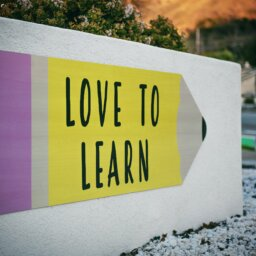 "A board in an outdoor setting, featuring an illustration of a pencil labelled ""love to learn"""