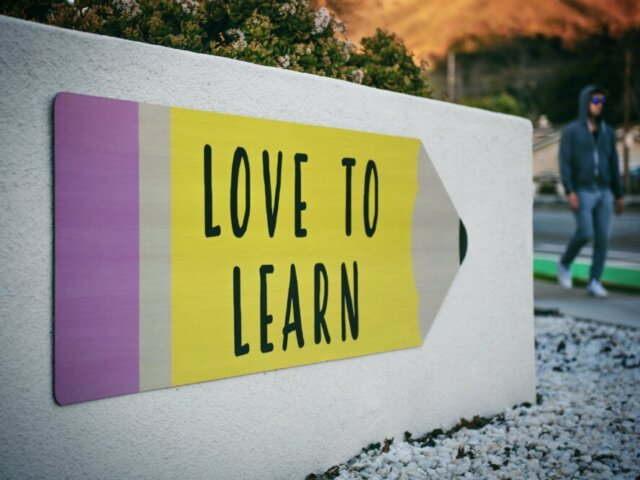 """A board in an outdoor setting, featuring an illustration of a pencil labelled """"love to learn"""""""