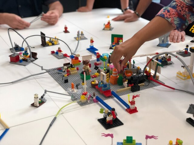 Several hands reach out to work on a Lego scene on a table