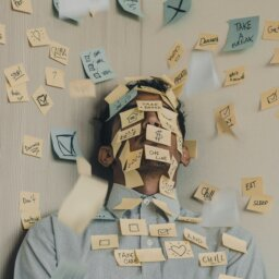 "A person covered in sticky notes with work-related messages and also messages like ""chill"" and ""take a break""."
