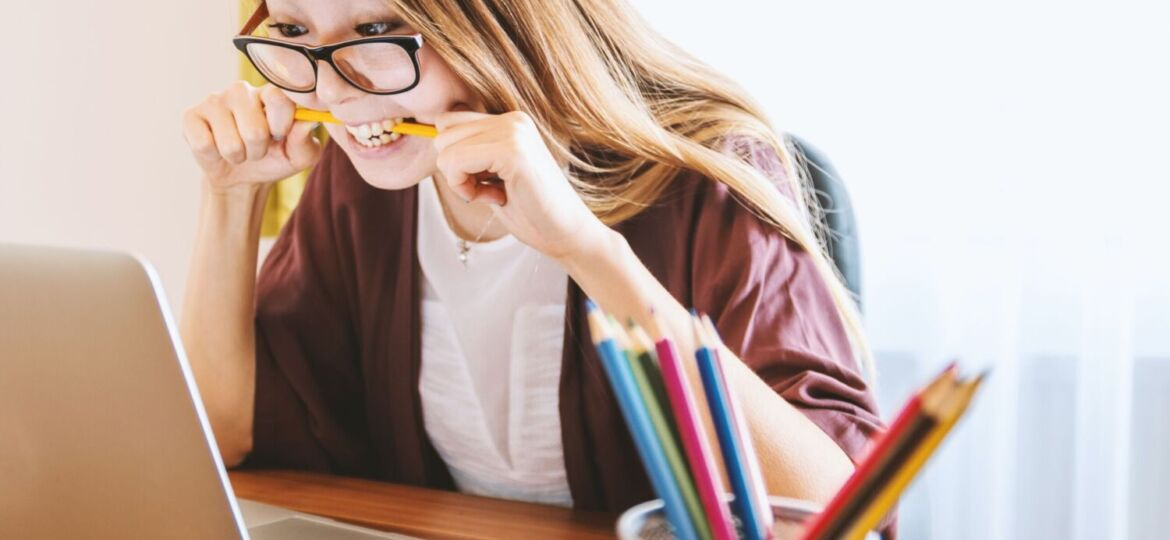 A wide eyed person leans over a laptop, biting a pencil.