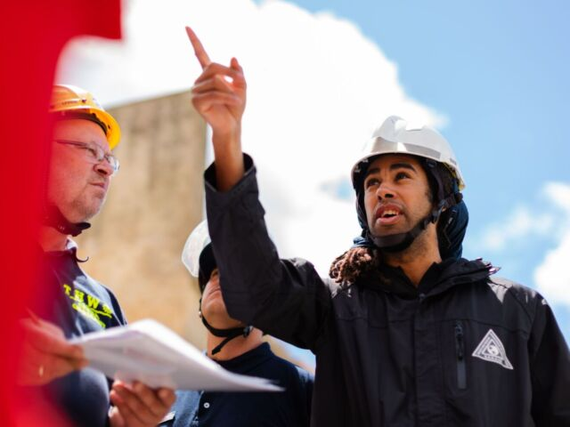 People on a sunny worksite converse, wearing hardhats
