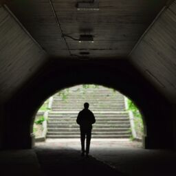 A silhouetted figure in a tunnel faces the entrance and the light-filled outside