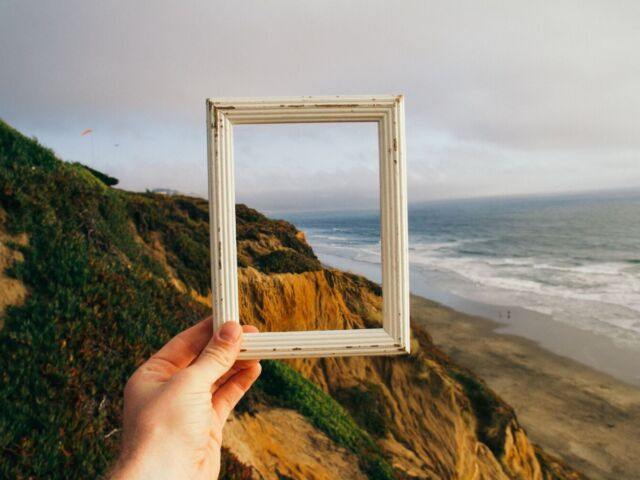 A hand reaches forward, holding a picture frame that frames a windswept coastal scene.