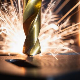 A close up of a drill bit, with sparks in the background