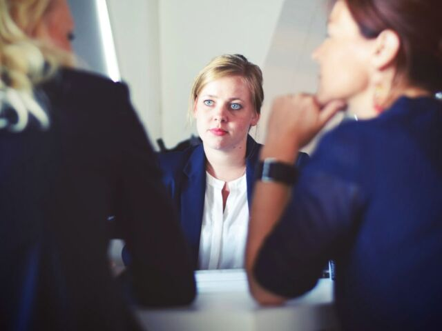 Focus on a woman at a meeting, with a troubled expression. Other women can be seen from the back.