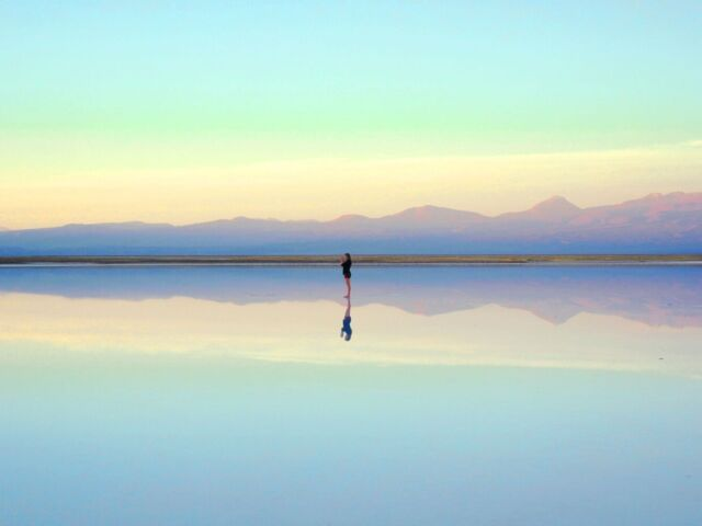 An image of a distant figure standing on water that reflects a sky lit by sunrise.